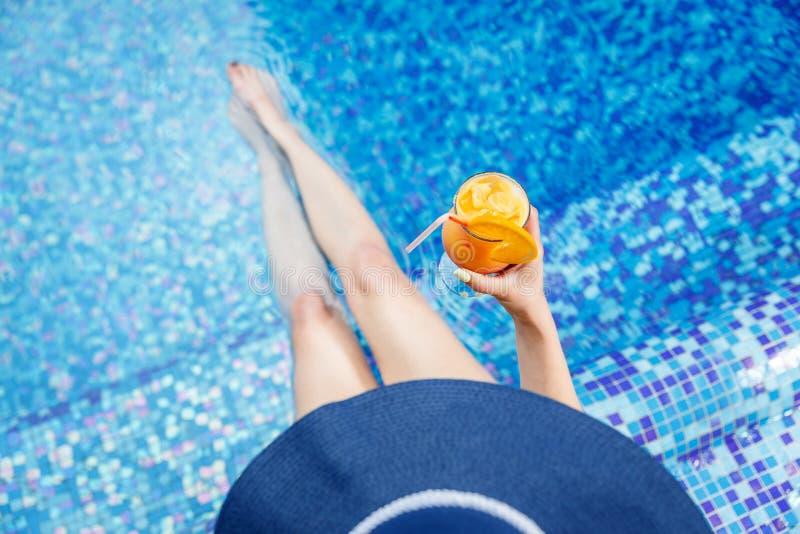 Frau in einem blauen Hut, der am Pool mit einem Cocktail sich entspannt stockfotografie