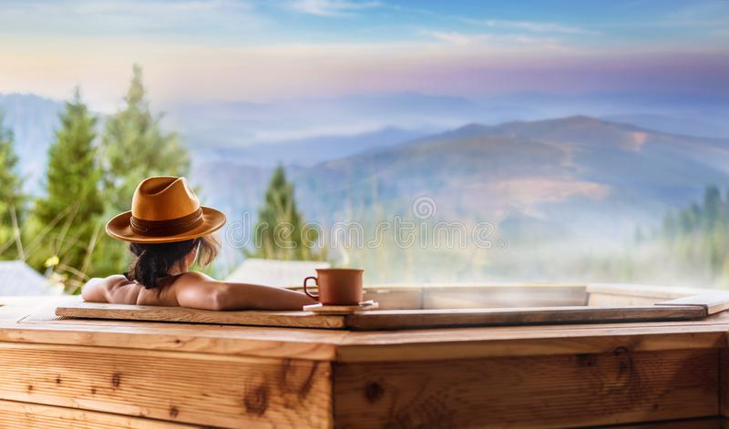 Frau in einem Freilichtbad mit Ansicht der Berge stockfotos