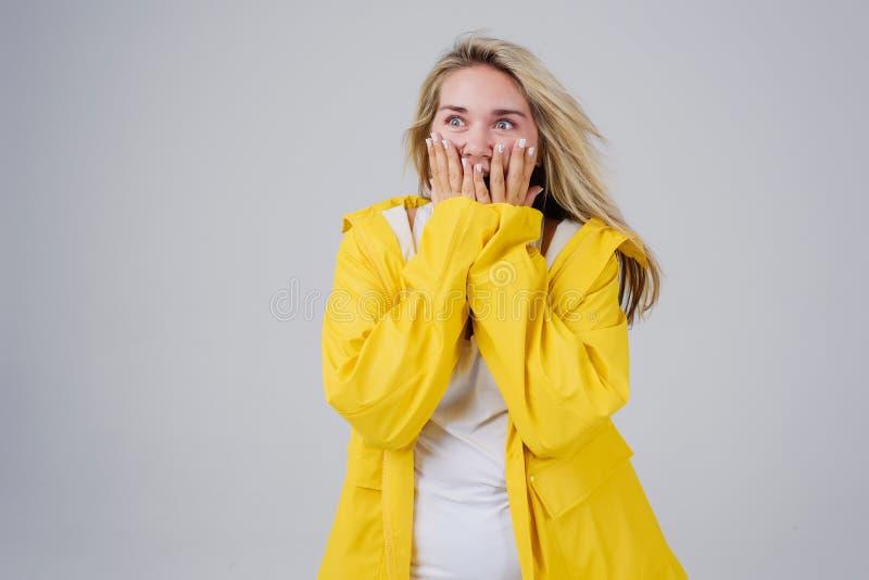 Frau in einem gelben Regenmantel auf einem grauen Hintergrund lizenzfreies stockbild