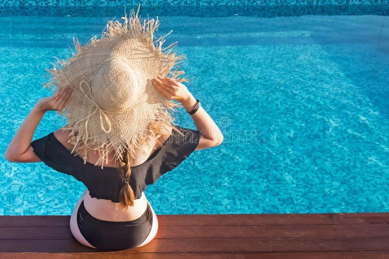 Frau in einem großen Strohhut, der nahe dem Swimmingpool die Sonne genießend sitzt lizenzfreies stockbild