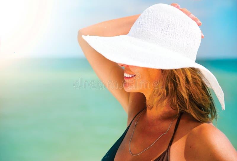 Frau in einem großen weißen Hut bräunend auf dem Strand lizenzfreie stockfotos