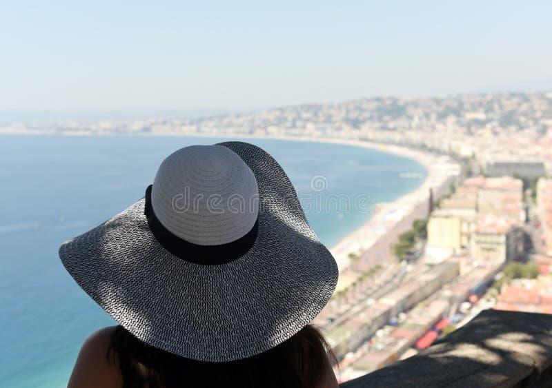 Frau in einem Hut betrachtet den Strand und die Promenade von Nizza lizenzfreie stockfotografie
