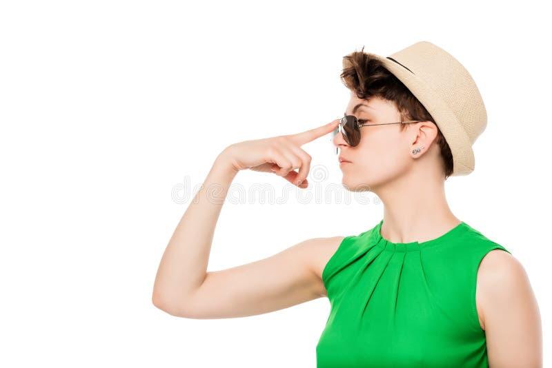 Frau in einem Hut justiert seine Sonnenbrille auf seiner lokalisierten Nase stockbilder