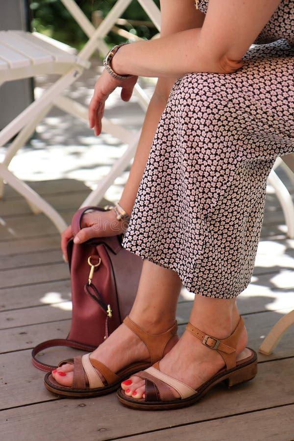 Frau in einem Kleid, das mit ihrer Hand auf ihrer Tasche sitzt lizenzfreie stockbilder