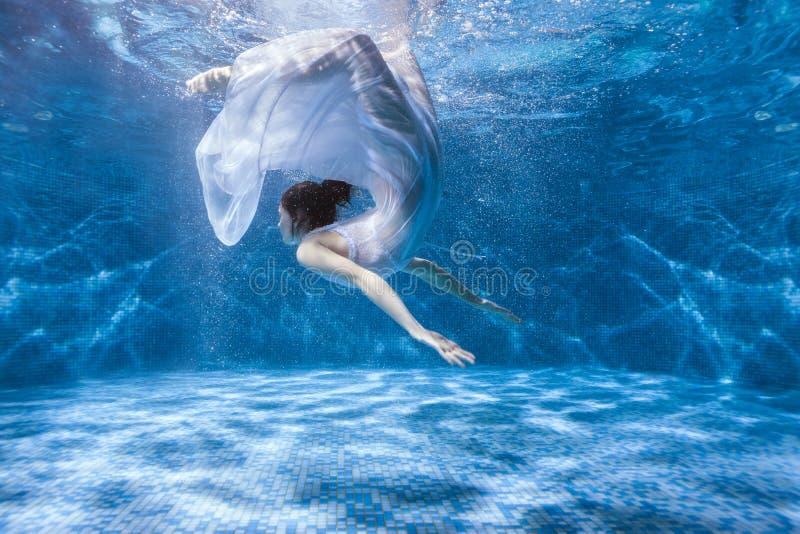 Frau in einem Kleid unter dem Wasser stockfotografie