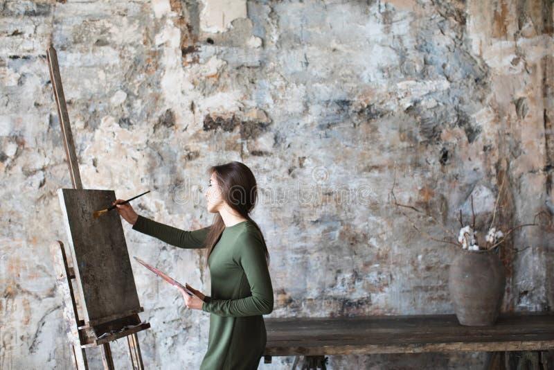 Frau in einem Kunststudio beim Zeichnen auf ein Segeltuch lizenzfreies stockbild