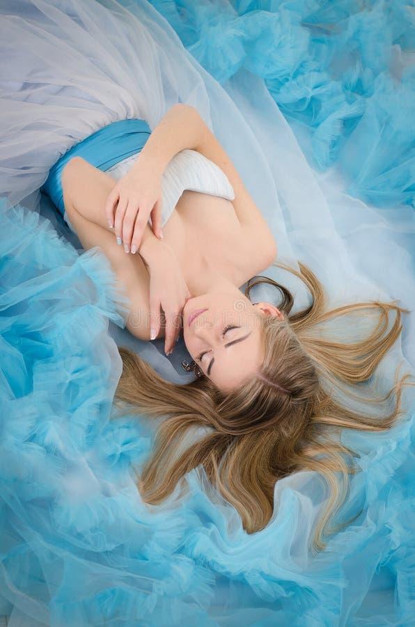 Frau in einem langen blauen Kleid stockfotografie