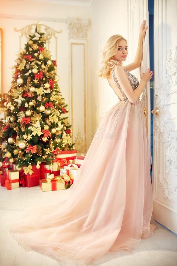 Frau in einem langen cremefarbenen Kleid, stehend nahe dem Weihnachtsbaum und der Tür Luxuriöse Blondine im Abendkleid feiern stockfotos