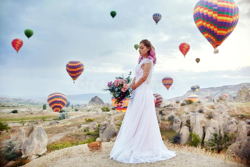 Frau in einem langen Kleid auf Hintergrund von Ballonen in Cappadocia Mädchen mit den Blumenhänden steht auf einem Hügel und scha stockbild