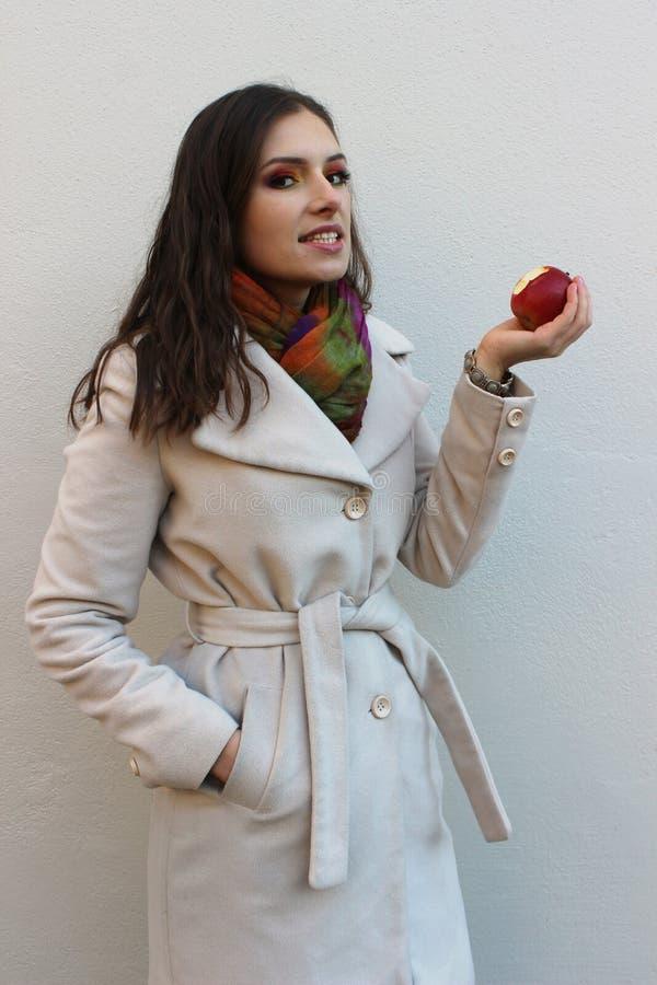 Frau in einem Mantel, der einen gebissenen roten saftigen Apfel hält stockfoto