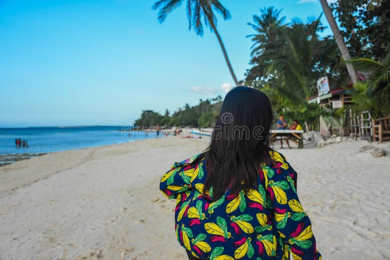 Frau in einem Mantel mit bunten Federn gehend auf einen bevölkerten Strand mit schönem Landschaftsbild lizenzfreie stockfotografie