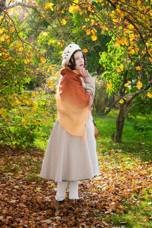 Frau in einem Mantel und in einem Barett im Park am Herbsttag stockbilder