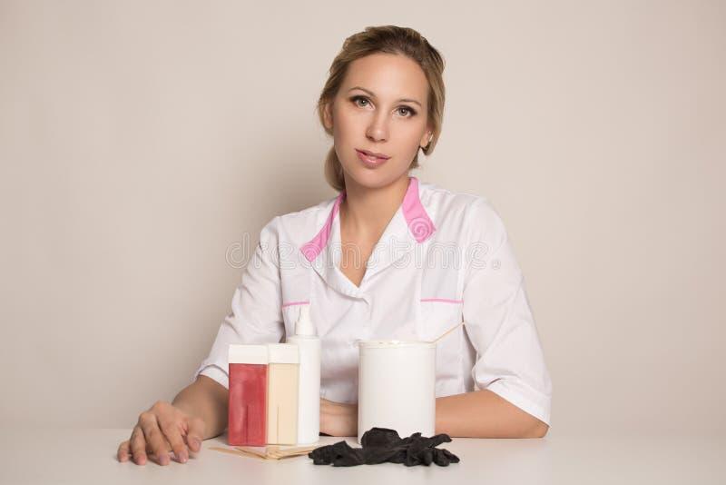 Frau in einem medizinischen Kleid mit Einzelteilen für Enthaarung lizenzfreie stockbilder