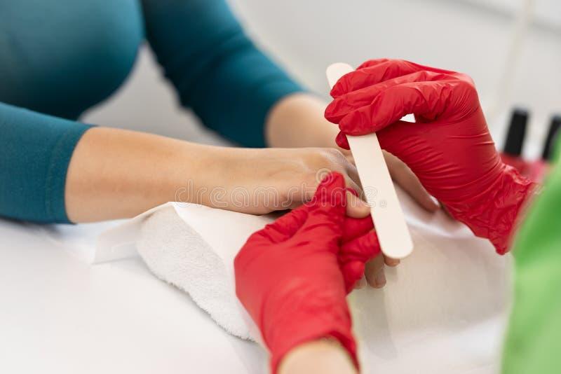 Frau in einem Nagelsalon, der eine Manik?re durch einen Kosmetiker mit Nagelfeile empf?ngt lizenzfreie stockfotos