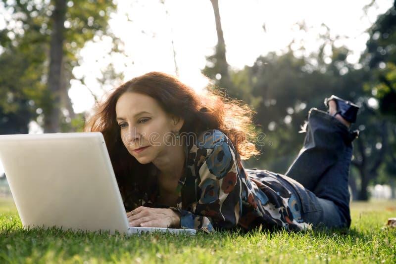 Frau in einem Park auf Computer stockfotos