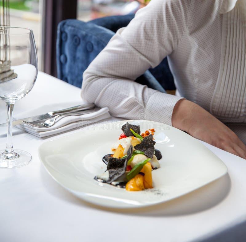 Frau in einem Restaurant einen schönen Fischsalat mit Früchten essend stockbild