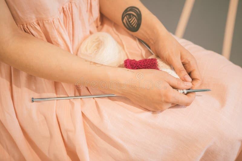 Frau in einem rosa Kleid setzte Stricknadeln und strickende Threads auf ihre Knie entspanntes nachdenkliches träumerisches Hobbys lizenzfreies stockfoto