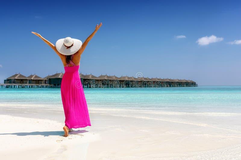 Frau in einem rosa Sommerkleid steht auf einem tropischen Strand in den Malediven stockfoto