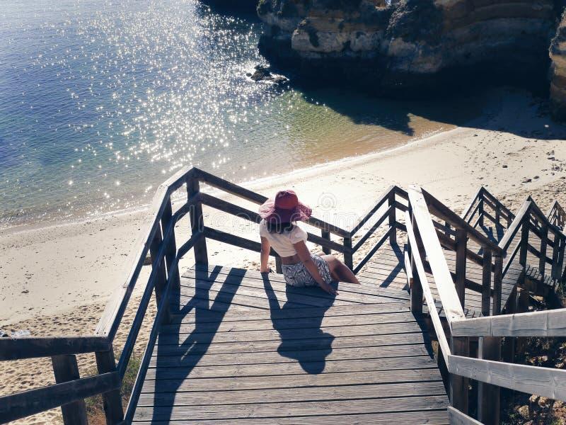 Frau in einem roten Hut auf den hölzernen Schritten der Treppe auf dem Strand in Portugal stockbilder