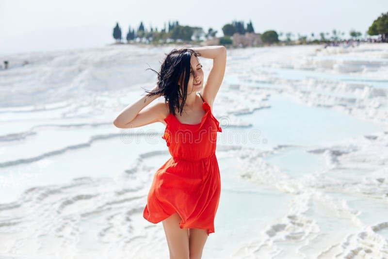 Frau in einem roten Kleid steht auf wei?en Travertinen M?dchen in der Sonne nahe der wei?en Wand Pamukkale lizenzfreies stockbild