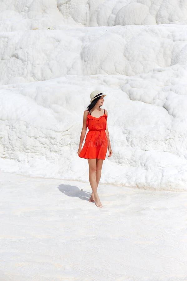 Frau in einem roten Kleid steht auf wei?en Travertinen M?dchen in der Sonne nahe der wei?en Wand Pamukkale lizenzfreies stockfoto