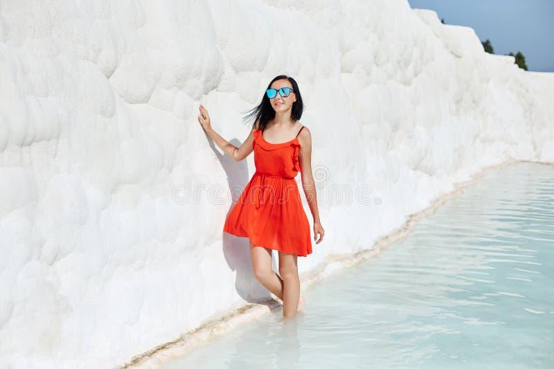 Frau in einem roten Kleid steht auf wei?en Travertinen M?dchen in der Sonne nahe der wei?en Wand Pamukkale stockfotos