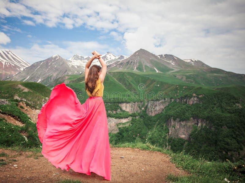 Frau in einem schönen Kleid in den Bergen stockbilder