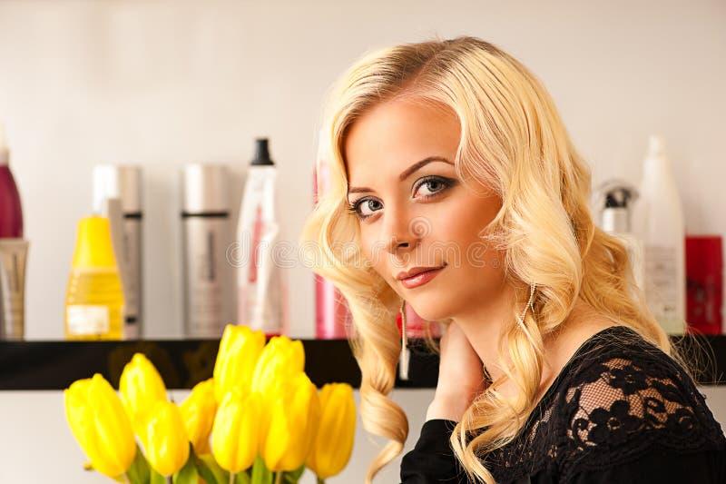 Frau in einem Schönheitssalon mit gelben Tulpen lizenzfreie stockbilder