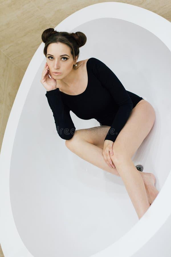 Frau in einem schwarzen Bodysuit im Badezimmer stockbild