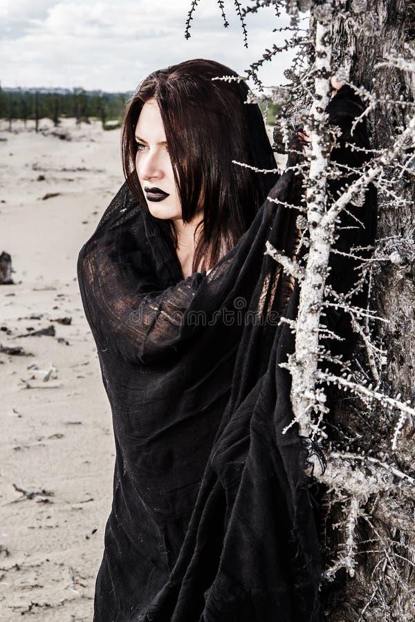 Frau in einem Schwarzen kleidet nahe dem trockenen Baum lizenzfreies stockbild