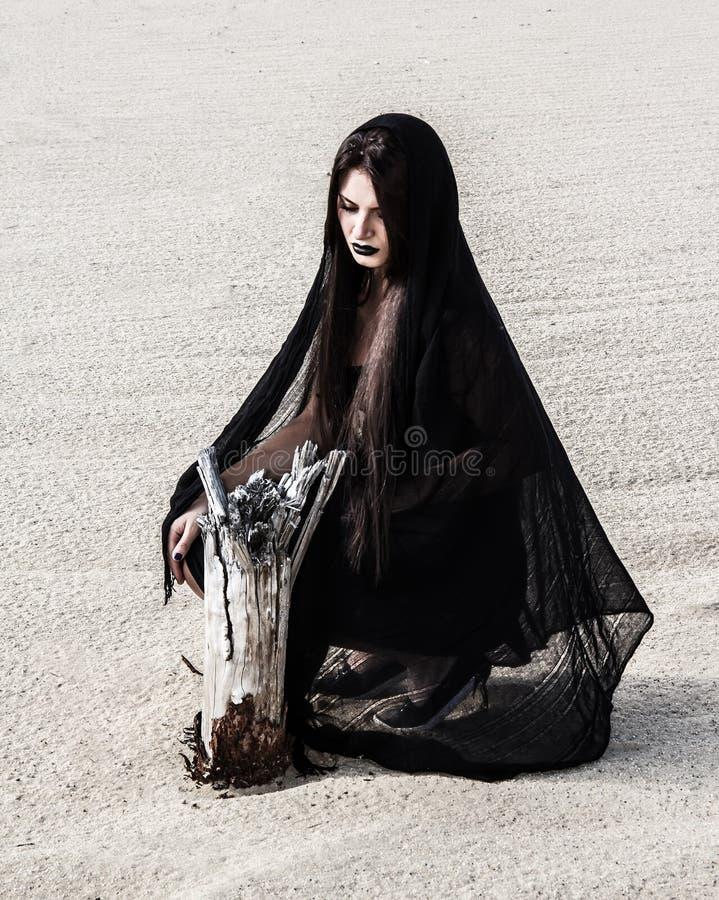Frau in einem Schwarzen kleidet nahe dem trockenen Stumpf stockfoto