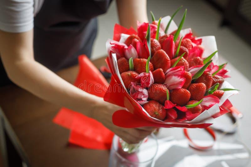 Frau in einem schwarzen Schutzblech setzt in einen Vase einen schönen ursprünglichen Blumenstrauß von Tulpen und von Erdbeeren ei lizenzfreie stockfotos
