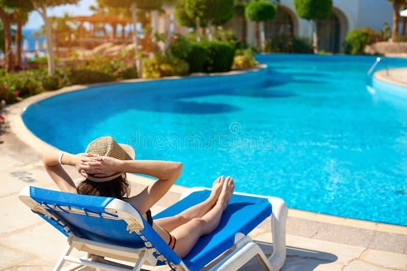 Frau in einem Strohhut, der auf einem Daybed nahe einem luxuriösen Sommerpool, Konzeptzeit zu reisen sich entspannt stockfotografie