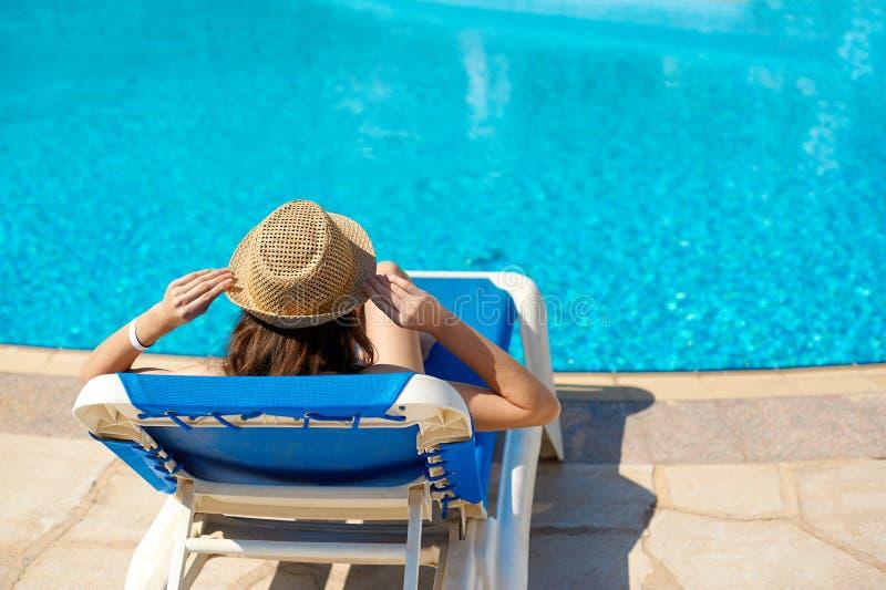 Frau in einem Strohhut, der auf einem Plattformstuhl nahe einem luxuriösen Sommerpool, Konzeptzeit zu reisen sich entspannt stockbilder