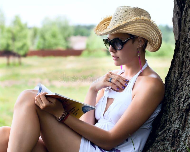 Frau in einem Strohhut ein Buch lesend lizenzfreie stockbilder