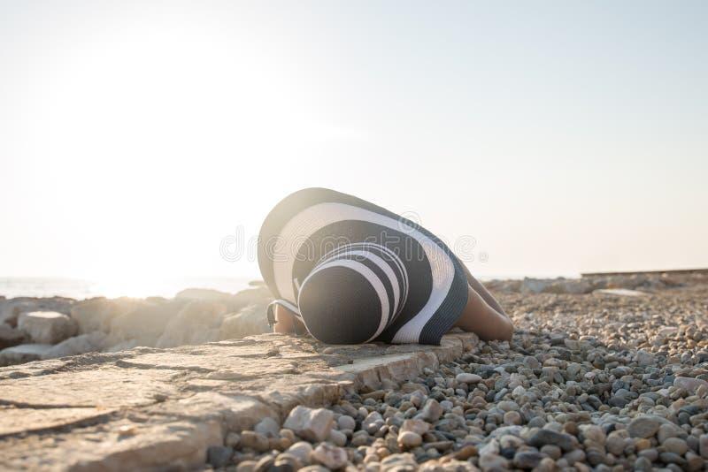 Frau in einem sunhat, das auf einem steinigen Strand sich entspannt lizenzfreie stockbilder