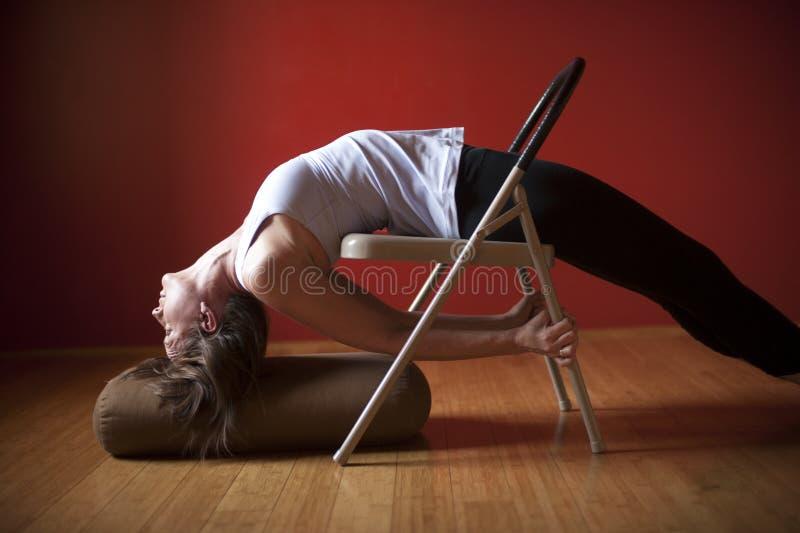 Frau in einem Yoga-Studio, das Restaurierungs- Asana übt lizenzfreie stockfotos