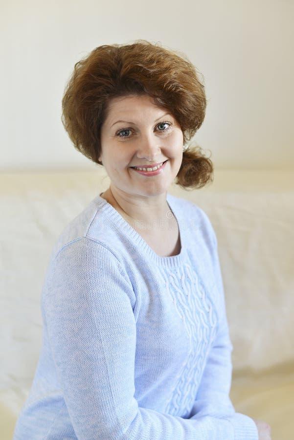 Frau in einer blauen Strickjacke, die auf einem Sofa sitzt stockfotos