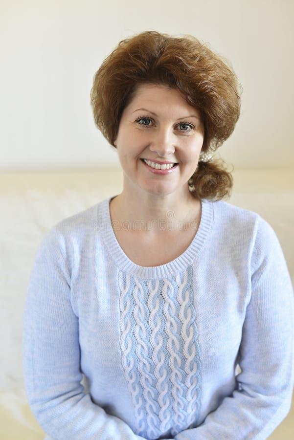 Frau in einer blauen Strickjacke, die auf einem Sofa sitzt stockfotografie