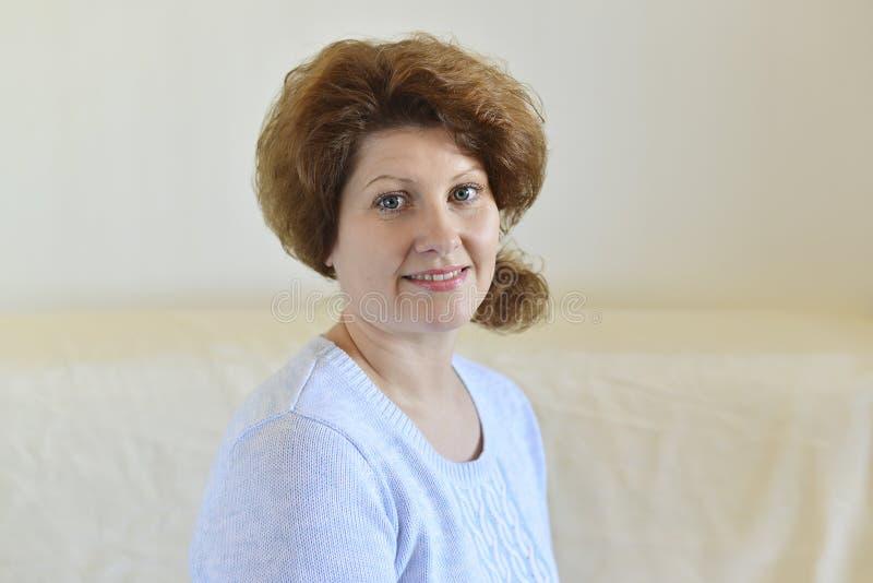 Frau in einer blauen Strickjacke, die auf einem Sofa sitzt lizenzfreie stockbilder