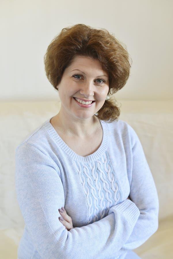 Frau in einer blauen Strickjacke, die auf einem Sofa sitzt lizenzfreie stockfotografie