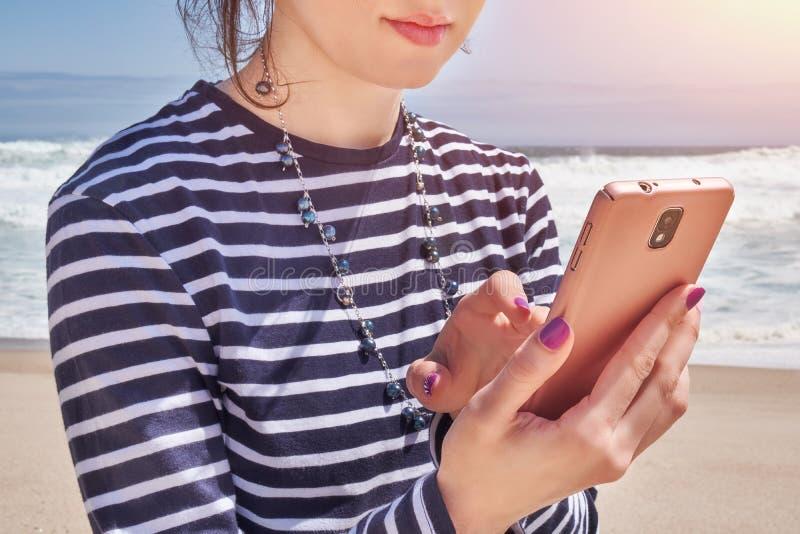 Frau in einer gestreiften T-Shirt Lesung im Smartphone auf Strand, Sommertag stockbild