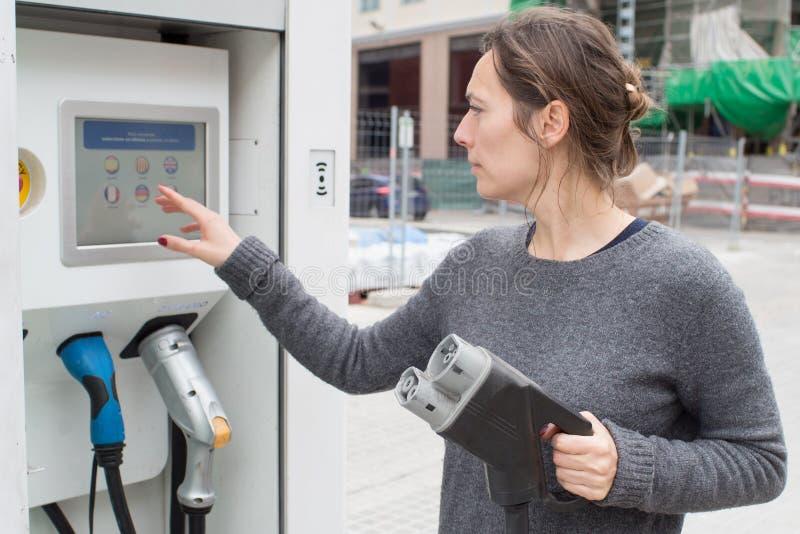Frau an einer Ladestation des Elektroautos lizenzfreie stockfotos