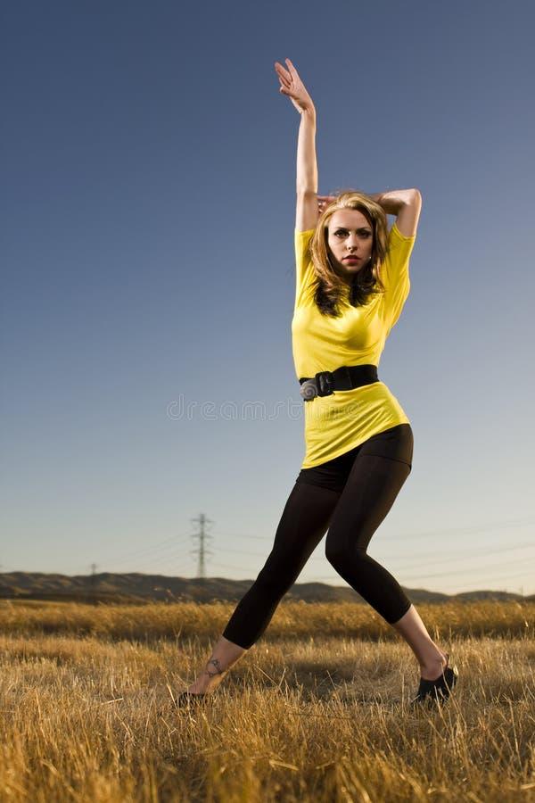 Frau in einer Tanz-Haltung auf einem Gebiet lizenzfreies stockbild