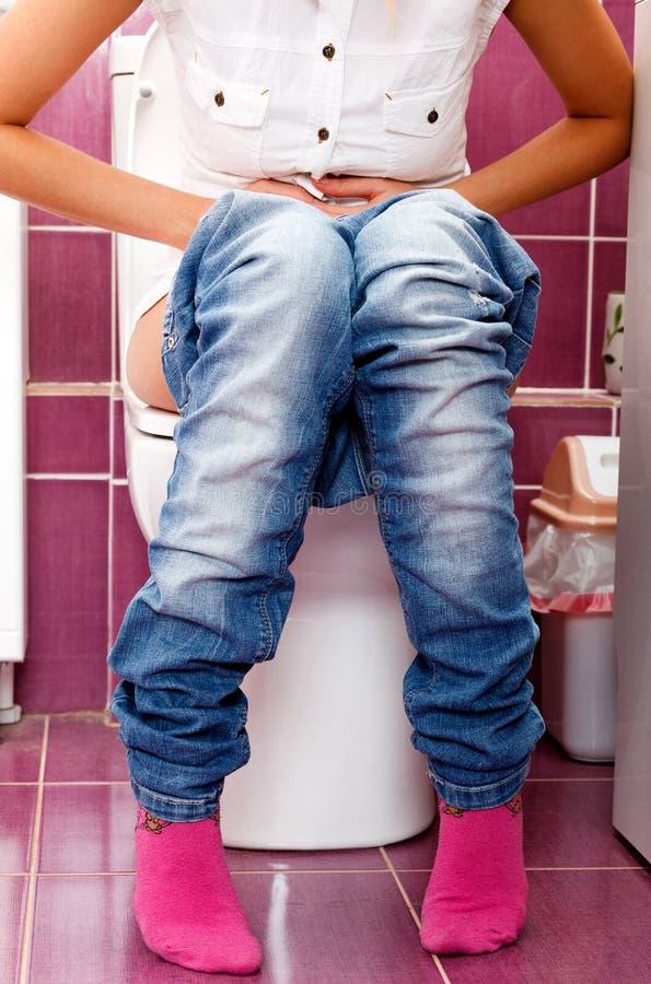 Frau in einer Toilette stockbild