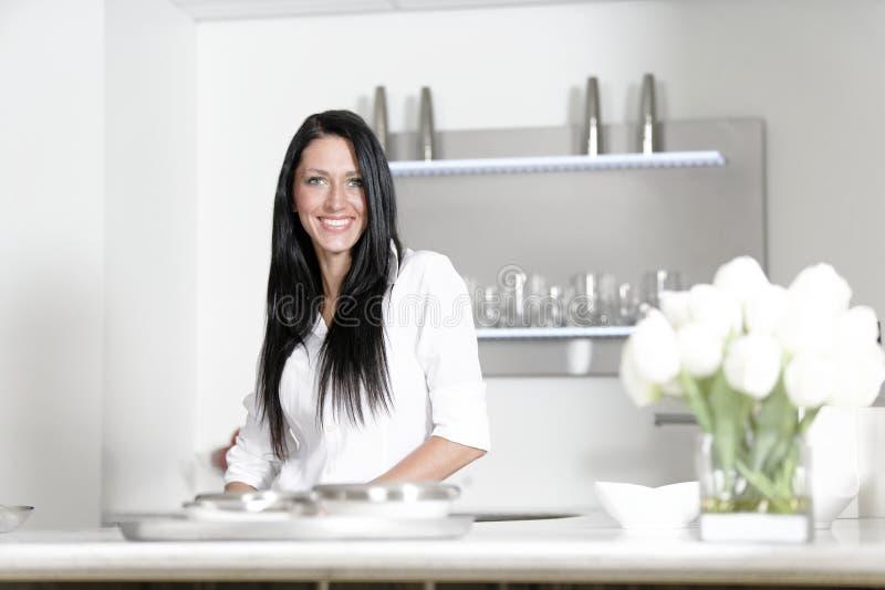 Frau in einer weißen Küche lizenzfreie stockfotos