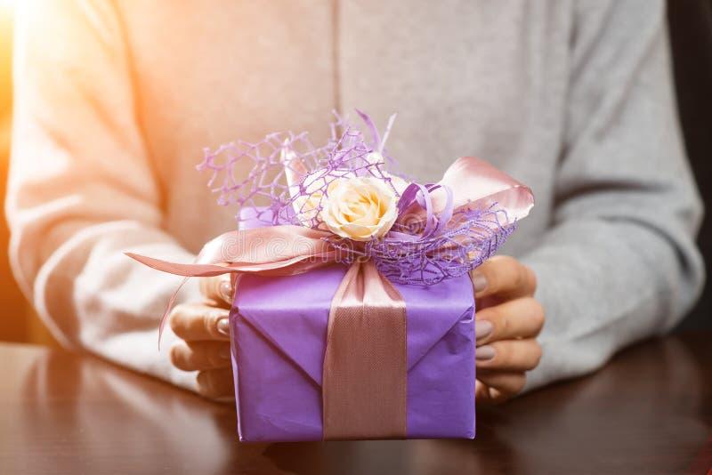 Frau empfing schöne purpurrote Geschenkbox mit Geschenk in den Strahlen von stockfoto