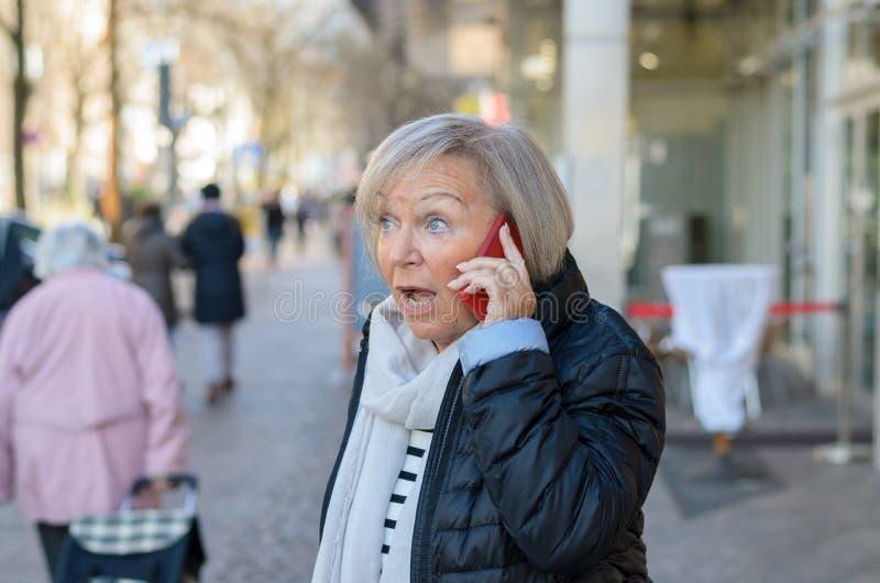 Frau entsetzte Unterhaltung durch das Telefon stockfotografie