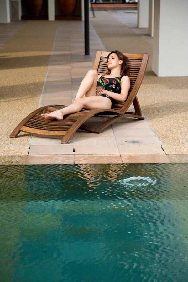 Frau entspannen sich durch die Poolseite stockbild