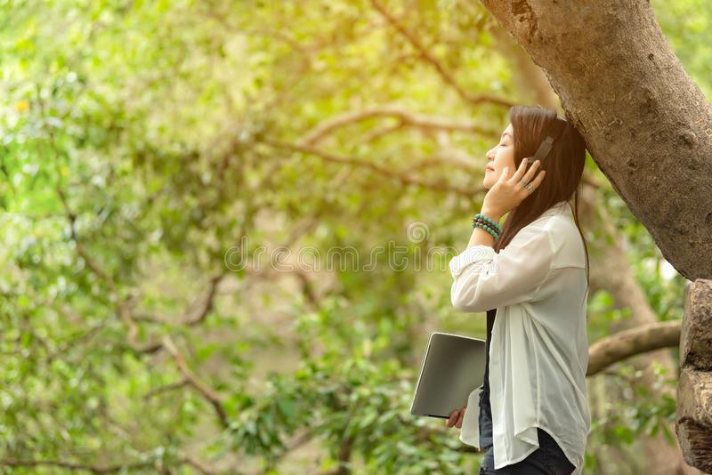 Frau entspannen sich und ein Buch lesend während hörende Musik mit Kopfhörer im Naturgrünpark, das glückliche Mädchen stockfoto